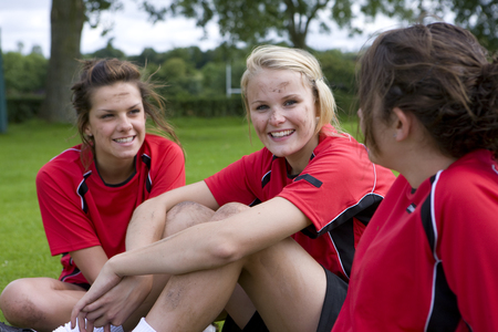 Portrait of smiling teenage girls in soccer uniforms Stock Photo