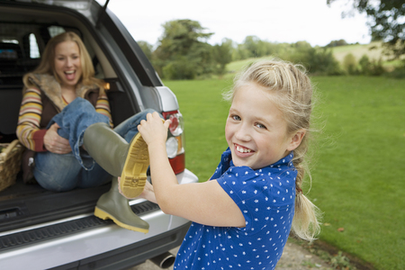 Girl (9-11) helping mother remove wellington boots, woman sitting in boot of car, smiling Stock Photo