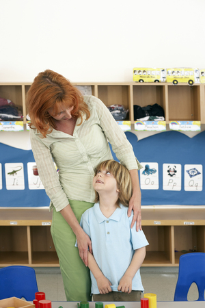 Boy (4-6) and teacher standing in classroom, smiling, woman looking down, schoolboy looking up Stock Photo
