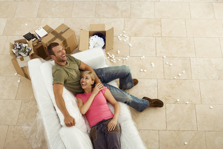 Couple moving house, resting on white sofa beside boxes, taking break, smiling, overhead view