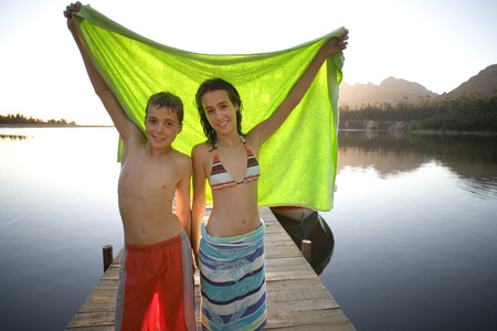 Teenage boy and girl (12-14) standing on lake jetty at sunset, holding aloft green towel, smiling, portrait Stock Photo