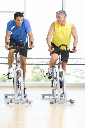 Two active men exercising on cycling machines in gym Reklamní fotografie