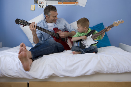 Father and son in bedroom at home playing electric guitars