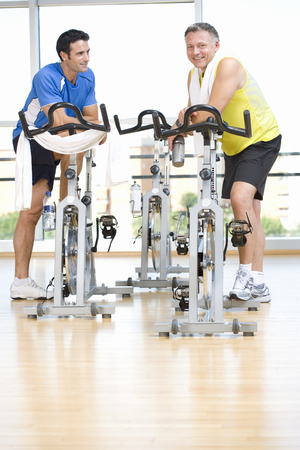 Two active men exercising on cycling machines in gym at camera