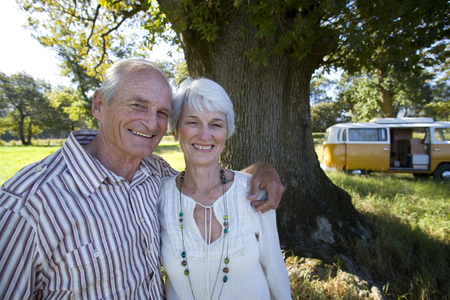 Senior couple on vacation in camper van in countryside at camera Stock Photo