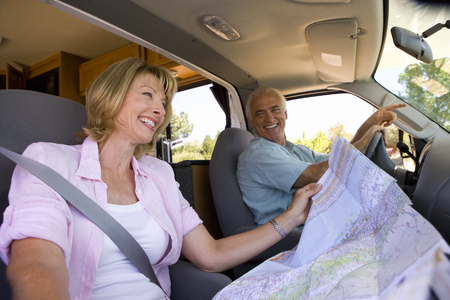 Mature woman reading map in motor home with husband driving Imagens