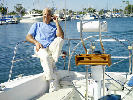 Senior man on boat in marina using mobile phone by wheel