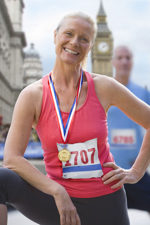 Mature female marathon runner with gold medal in London UK at camera