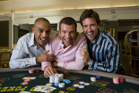 Young Men at roulette table in casino holding gambling chip at camera Stok Fotoğraf