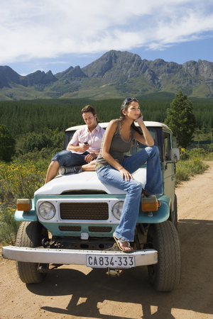 Couple on road trip on bonnet of jeep in countryside with mobile phone