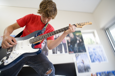 Teenage boy playing electric guitar in bedroom Imagens