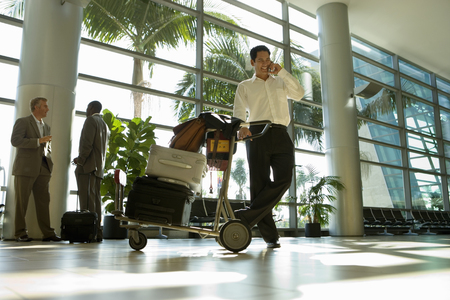 Businessman with luggage trolley in airport terminal using phone