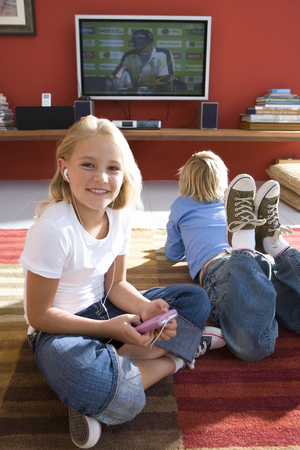 Children on rug by television watching and listening to mp3 player 스톡 콘텐츠