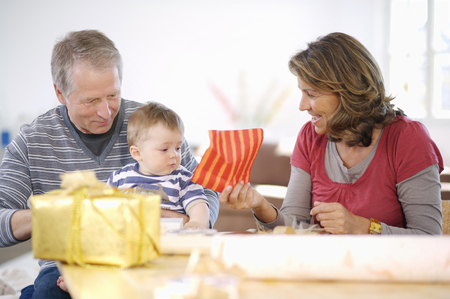 Grandparents with young grandson wrapping presents together at table 스톡 콘텐츠