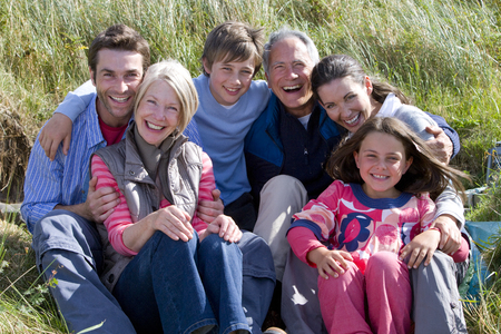 Portrait of smiling multi-generation family sitting on beach by dunes