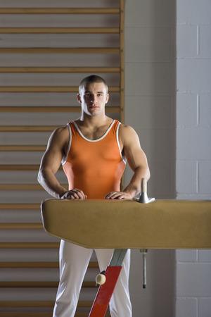 Portrait of male gymnast standing by pommel horse in gym Foto de archivo - 119536174