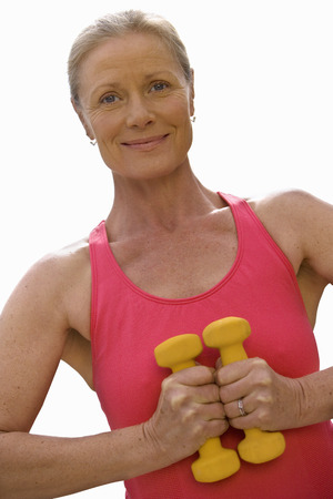 Cut out of active mature woman exercising with weights at camera