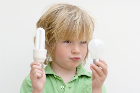 Energy concept as boy holds conventional and energy saving lightbulbs Imagens