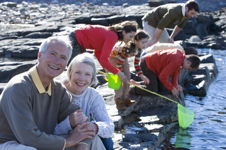 Multi-generation family fishing in rock pool on beach at camera Stock Photo