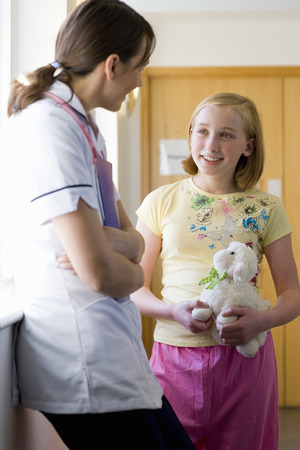 Nurse talking to girl patient holding toy in hospital corridor Imagens