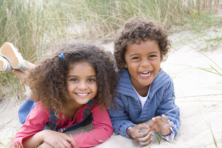 Portrait of smiling boy and girl lying in sand dunes on beach