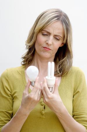 Woman choosing between conventional and energy saving lightbulbs