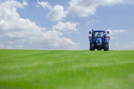 Tractor spreading fertilizer on crops in farm field against blue sky Standard-Bild - 119568643