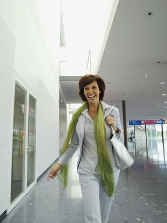 Portrait of smiling businesswoman walking through office foyer