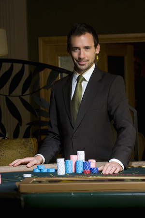 Portrait of man standing at casino table with gambling chips Stock Photo