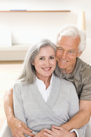 Portrait of smiling senior couple hugging at home together Imagens