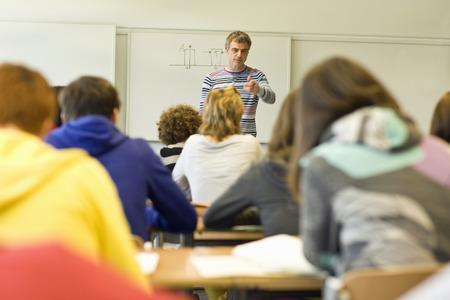 Male high school teacher standing at front of class teaching Imagens - 119569355