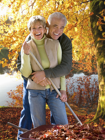 Smiling senior couple collecting autumn leaves in garden at camera