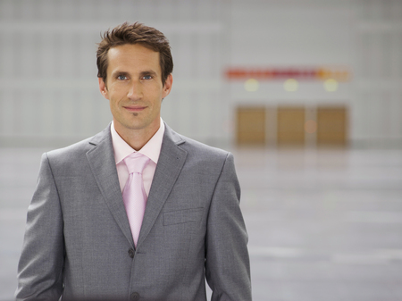 Portrait of businessman in large open plan conference center space