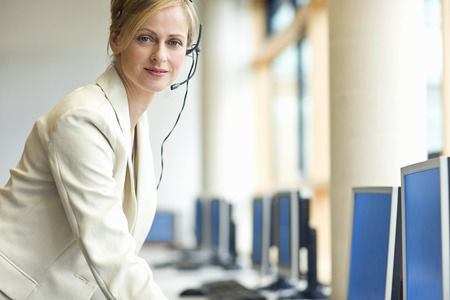 Businesswoman talking on phone using headset in sales office at camera Imagens