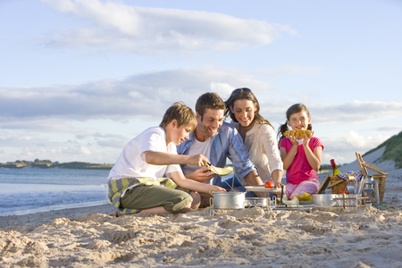 Family having barbecue picnic on sandy beach