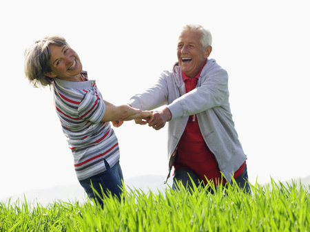 Loving senior couple holding hands on walk in countryside at camera