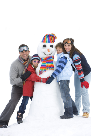 Cut out of family on winter vacation making snowman at camera