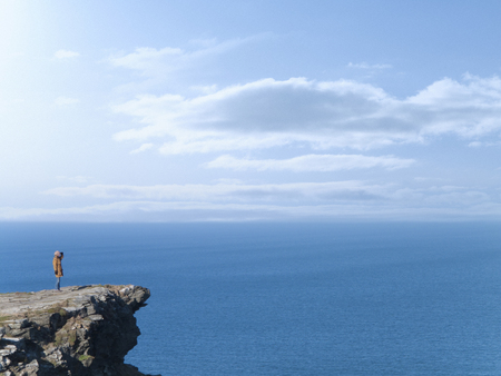 Adventurous woman standing on rocky cliff overlooking blue ocean 스톡 콘텐츠