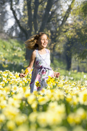 Smiling young girl running through field of spring daffodils