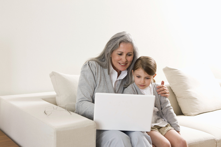 Grandmother and granddaughter using laptop at home Stock Photo