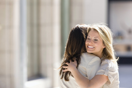 Two female friends meeting in city and hugging