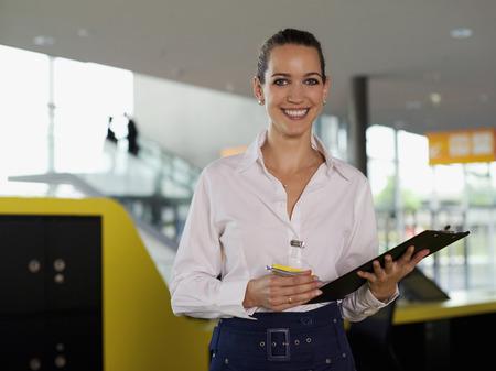 Portrait of smiling businesswoman holding clipboard in office Reklamní fotografie