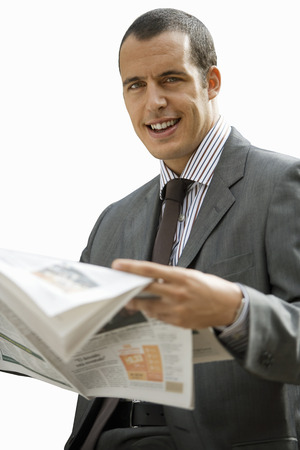 Cut out of smiling businessman reading newspaper at camera