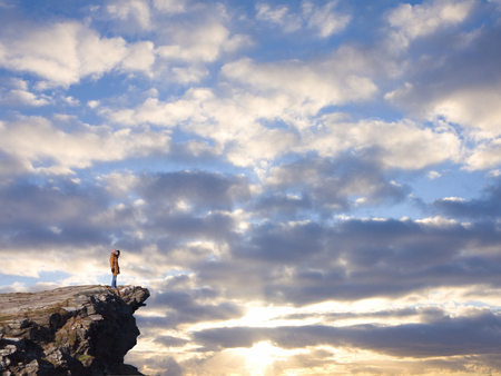 Adventurous woman standing on rocky cliff against dramatic sunset Stock Photo