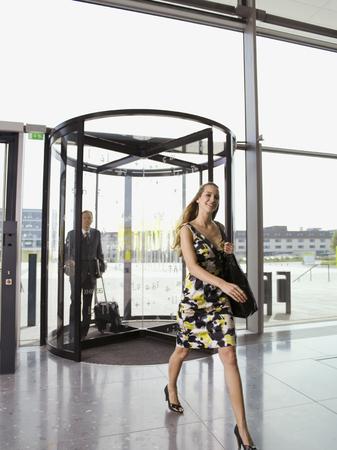 Businessman and businesswoman walking through revolving office door