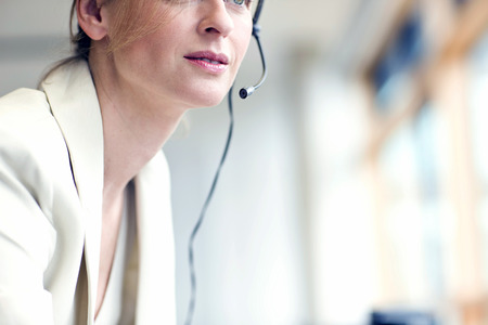 Detail of businesswoman talking on phone using headset in sales office Imagens