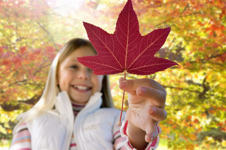 Girl holding red maple leaf on walk in autumn forest 写真素材