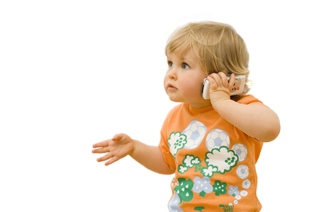 Cut out of young child playing and talking on toy mobile phone