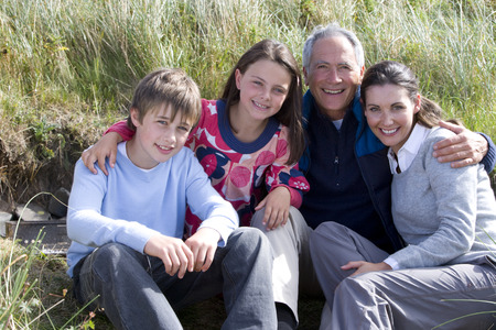 Grandfather with adult daughter and grandchildren sitting on beach
