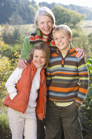 Portrait of grandmother with grandchildren in autumn countryside